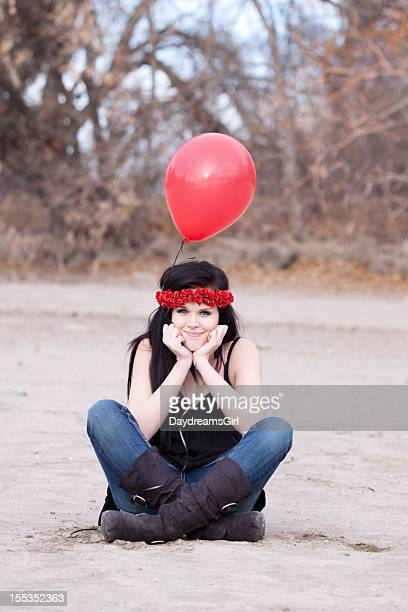 Happy Woman Sitting on Sandy Beach Holding Red Balloons
