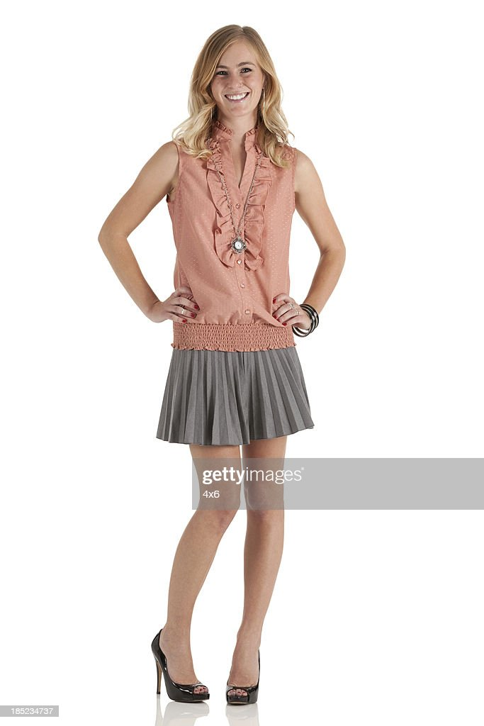 Happy woman standing with her arms akimbo