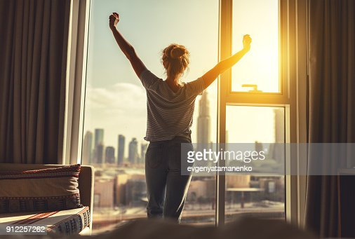 happy woman stretches and  opens curtains at window in morning : Stock Photo