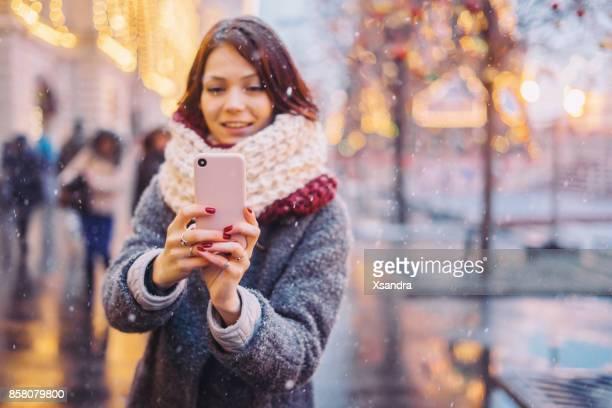 Glückliche Frau fotografieren auf die Weihnachtszeit dekoriert Straße