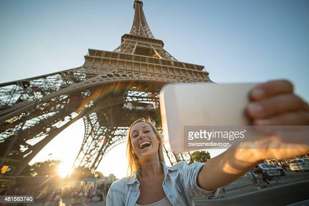 Happy woman taking selfie under Eiffel tower