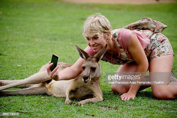 Happy Woman Taking Selfie With Kangaroo On Grassy Field