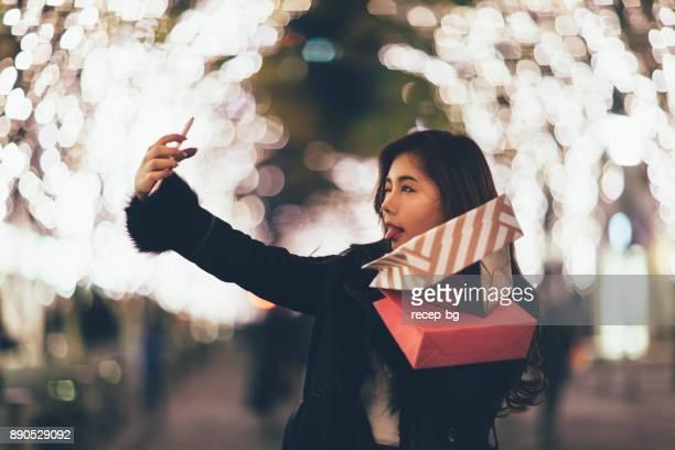 ショッピング バッグと Selfie を取って幸せな女