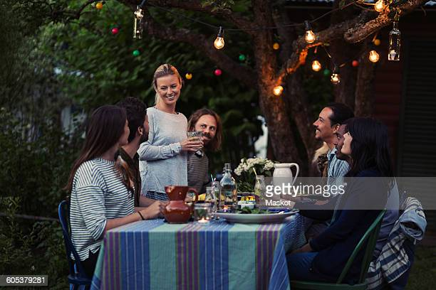 Happy woman talking to friends sitting at dinner table in yard
