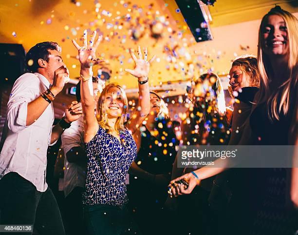Glückliche Frau werfen confeti bei einer Feier mit Freunden
