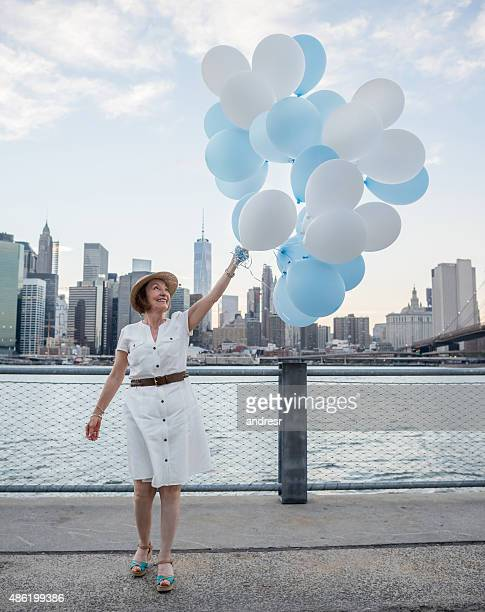Happy woman tourist holding balloons in New York