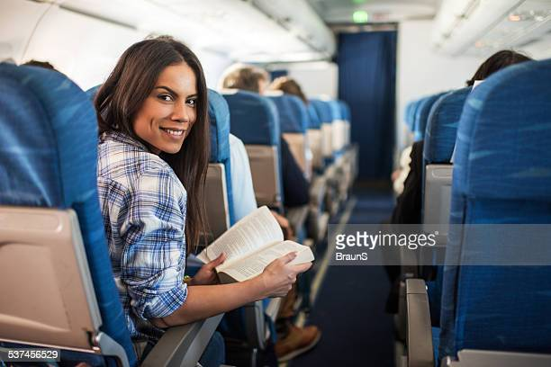 Happy woman traveling by airplane.