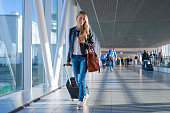 Happy woman travelling and walking in airport, concept of travelling light
