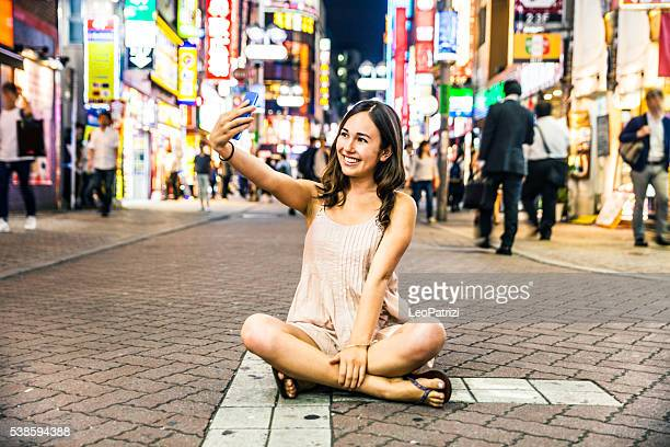 Happy woman travels in Tokyo, Shibuya crossing at night