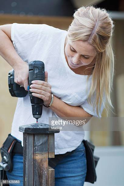 Happy woman using cordless screwdriver on wooden post