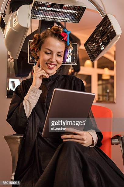 Happy woman using digital tablet under hair dryer at hairdressers.