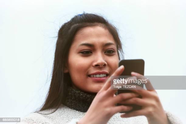 Happy woman using smartphone, Helsingborg, Sweden