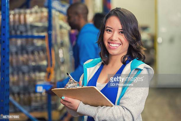 Happy woman volunteering in charity food bank warehouse, taking inventory