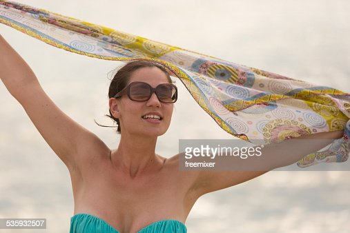 Happy woman walking on a beach with scarf : Stock Photo