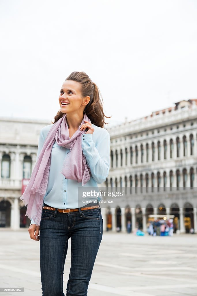Happy woman walking on piazza san marco in venice, italy : Stock Photo