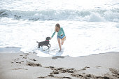 happy woman walking on the beach playing with her dog
