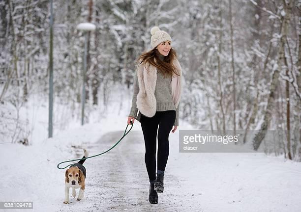 Happy woman walking/ running with beagle dog winter walk path