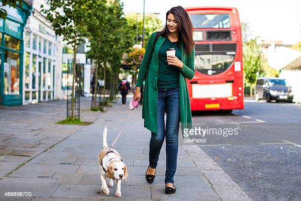 Happy woman walking with dog in early Sunday morning