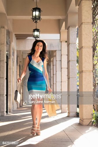 Happy woman walking with shopping bags.