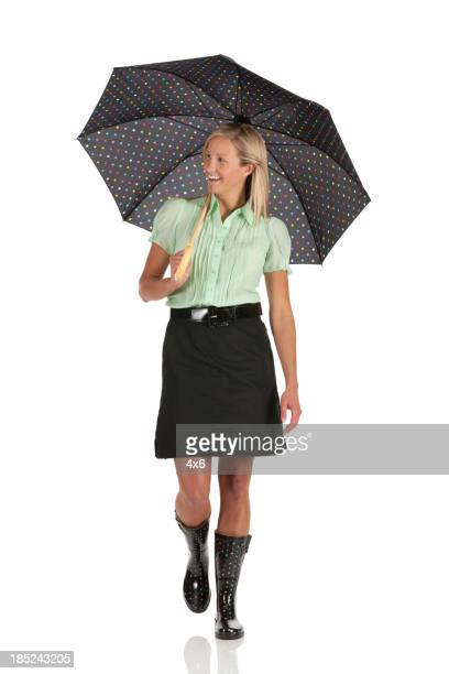 Happy woman walking with umbrella