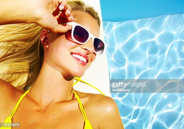 Happy woman wearing sunglasses and resting by swimming pool