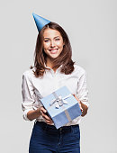 Happy woman wearing party hat giving a gift, isolated on grey background