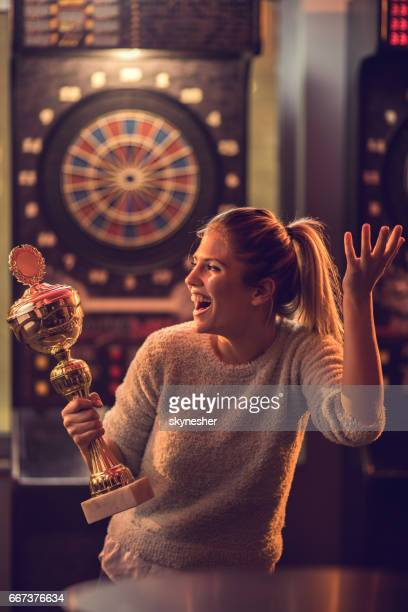 Happy woman with a trophy celebrating victory in dartboard game.