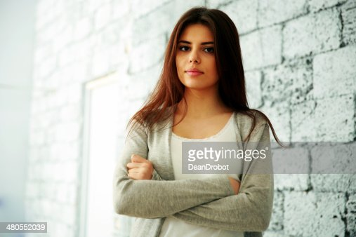 happy woman with arms folded standing : Stock Photo