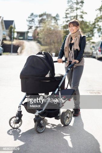 Happy woman with baby carriage standing on sunny street