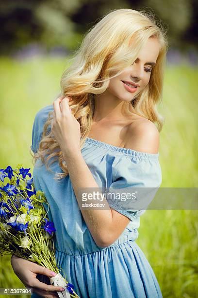 Heureuse femme avec bouquet de fleurs violettes