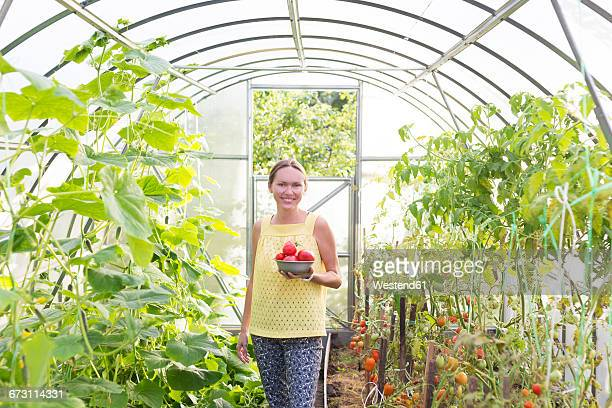 Happy woman with bowl of harvested tomatoes in a greenhouse