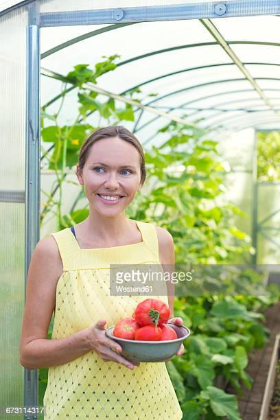 Happy woman with bowl of harvested tomatoes in front of greenhouse