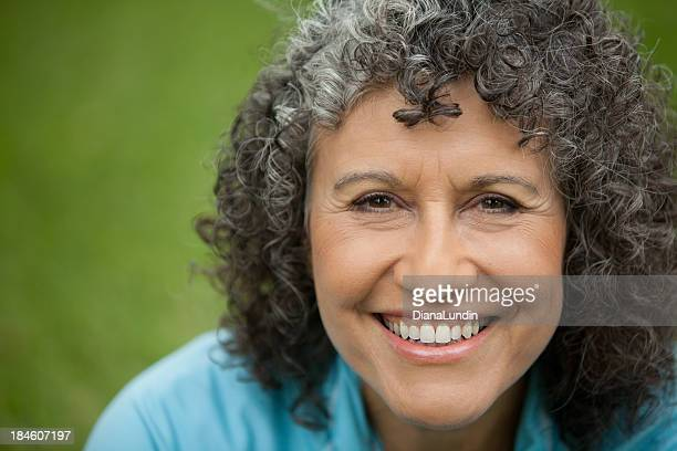 Happy woman with curly hair in front of a green background