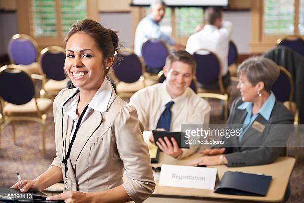 Femme heureuse avec des matériaux à une conférence