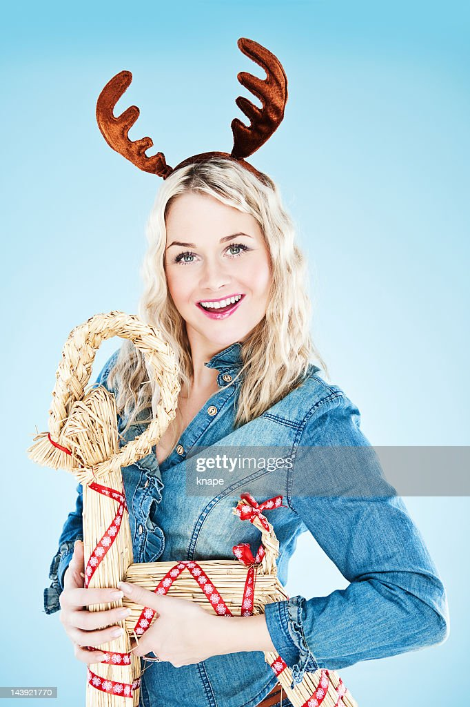 Happy woman with reindeer horns and straw goat : Stock Photo