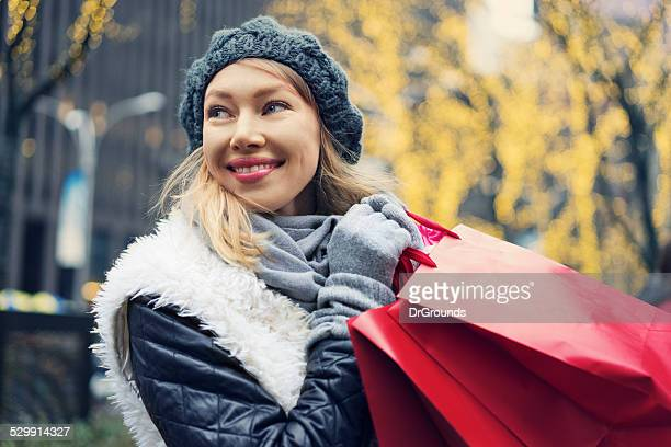 Happy woman with shopping bags winter season