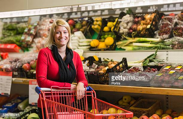 Happy woman with shopping cart at store