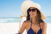 Young woman in blue bikini sitting on deck chair wearing white straw hat. Happy girl enjoying summer vacation at beach. Portrait of beautiful latin woman relaxing at beach with sunglasses looking away