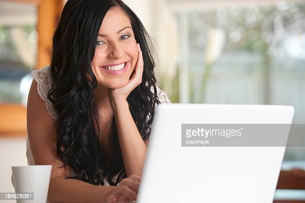 Glückliche Frau arbeitet auf einem laptop