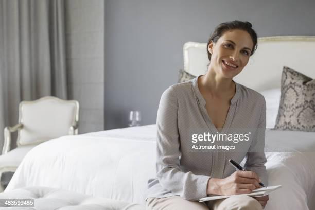 Happy woman writing in bedroom