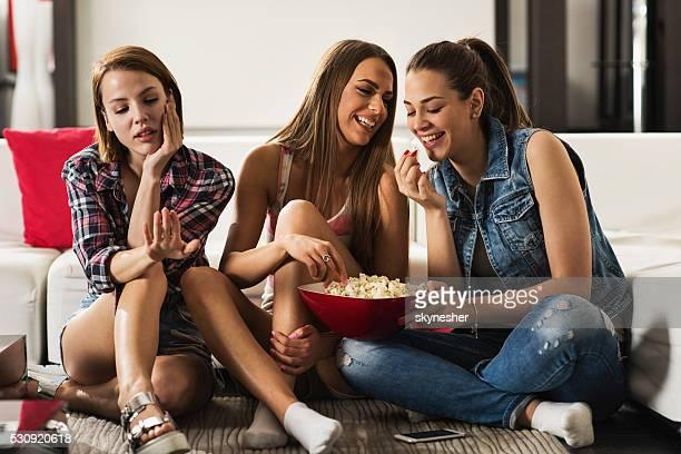 Donna felice a casa mangiando pop-corn e considerato che ignora le loro amico.