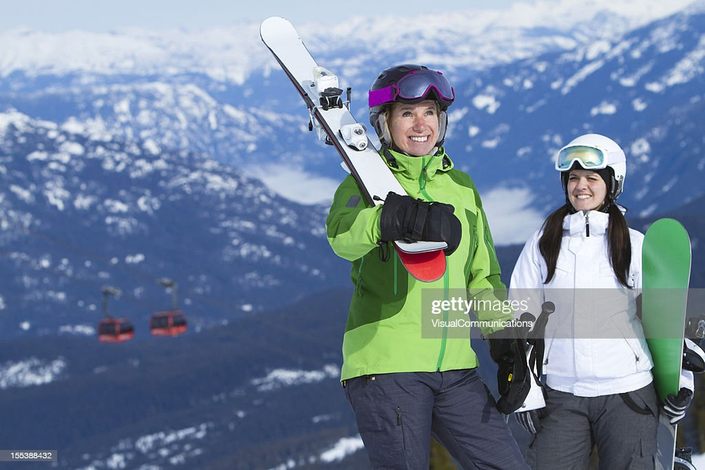 Happy women carrying ski and snowboard gear : Stock Photo