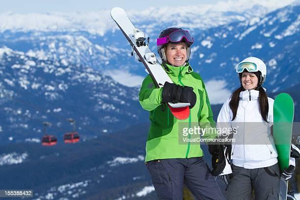 Glückliche Frauen tragen ski und snowboard-Ausrüstung