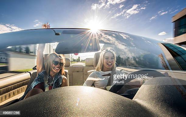 Happy women having fun on a road trip in convertible.