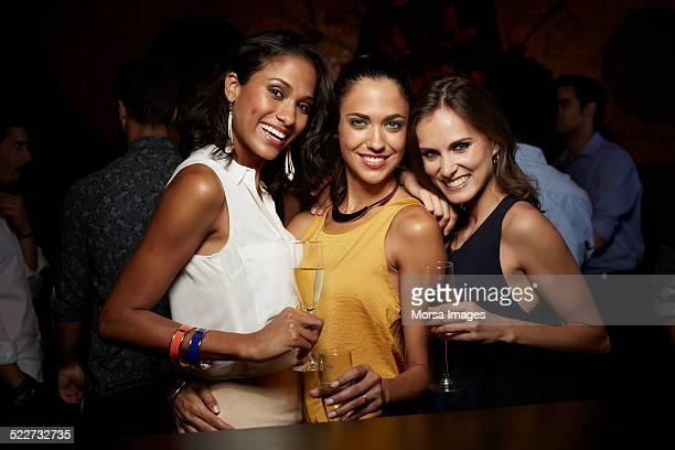 Happy women holding champagne flutes in nightclub