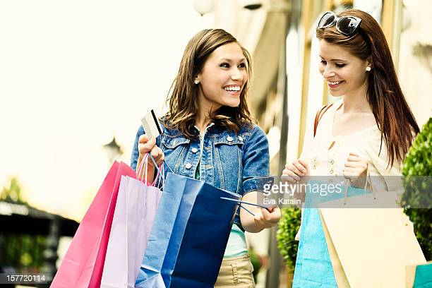 Happy women posing with shopping bags