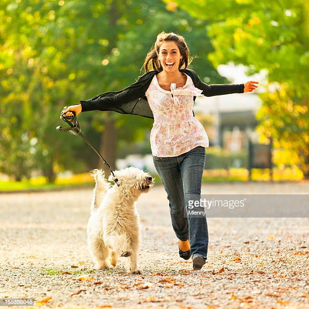 Happy women running with her dog in the park