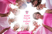 Happy women smiling in circle wearing pink for breast cancer against breast cancer awareness message