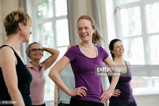 Donne felice parlando mentre vi rilassate in palestra