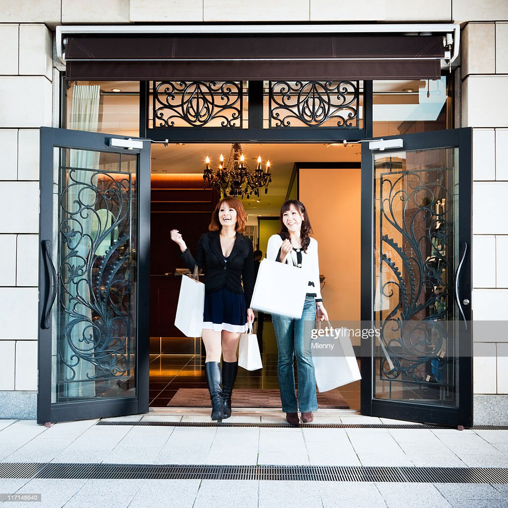 Happy women walking out of luxury boutique stock photo for Luxury boutique